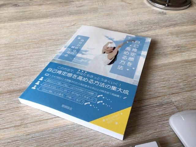 「自己肯定感を高める方法」の「A5サイズの紙の本」は、こんな感じです!リモコンと並べて置いてあるので、サイズ感がわかると思います☆
